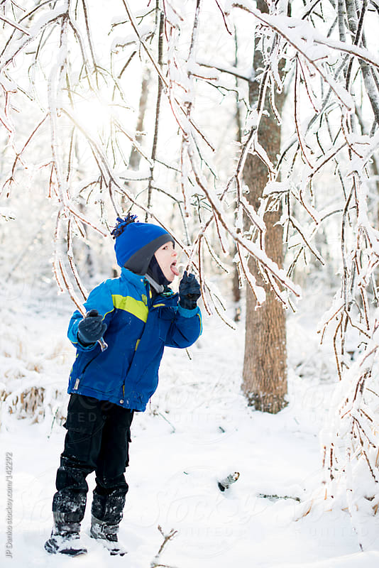 Little Boy Licking Icicle in Cold Winter Woods With Frozen Ice and Snow by JP Danko for Stocksy United