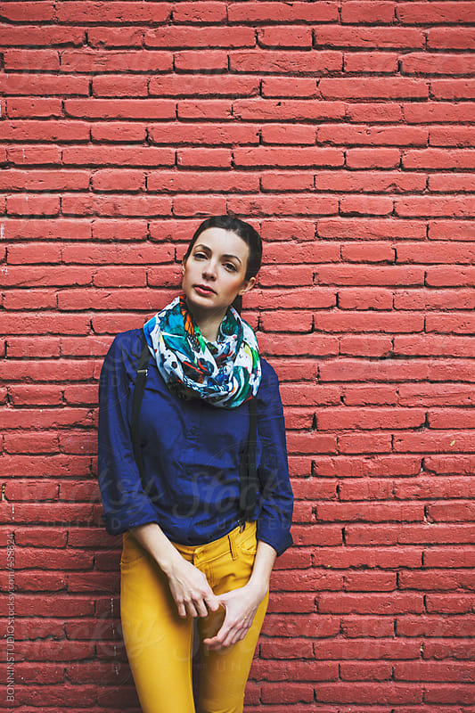 Beautiful woman standing in front red brick wall. Looking at camera. by BONNINSTUDIO for Stocksy United