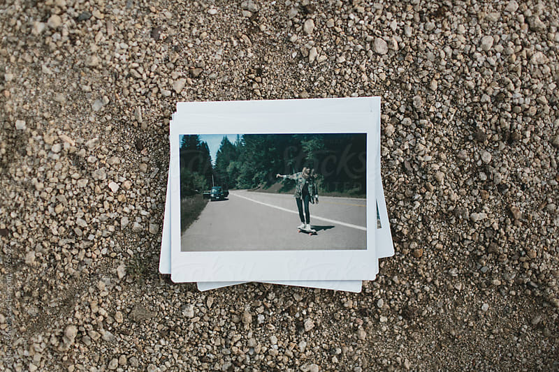stack of instant photos from road trip on ground by Nicole Mason for Stocksy United