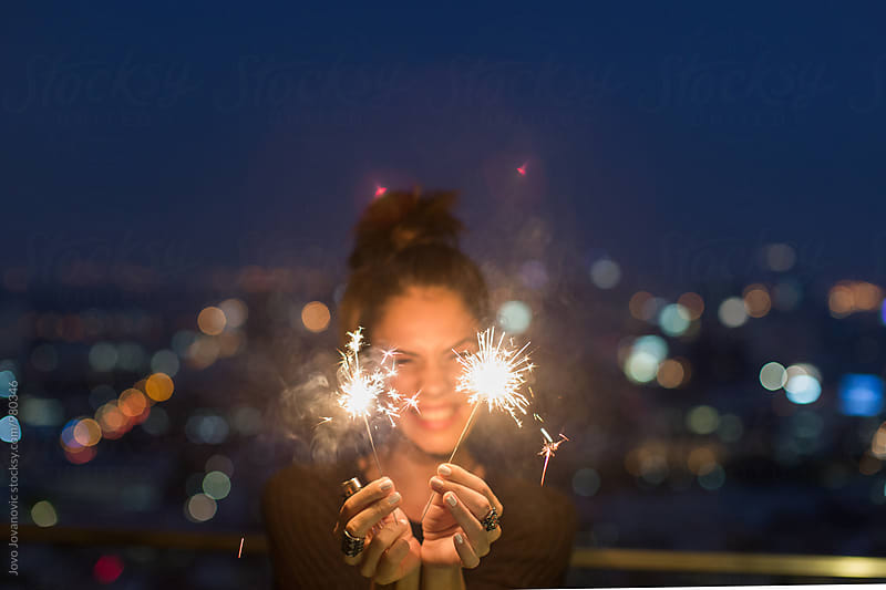 Happy caucasian woman holding sparklers by Jovo Jovanovic for Stocksy United