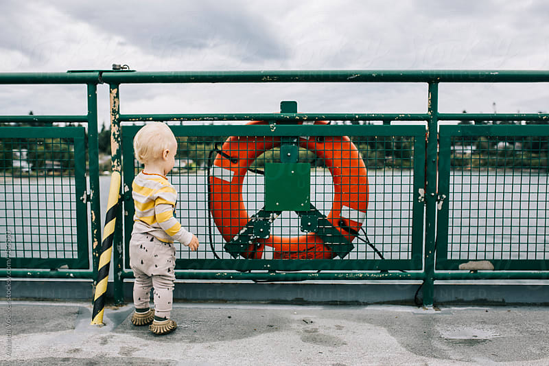 Toddler boy Looks off the side of a ferry by Amanda Voelker for Stocksy United