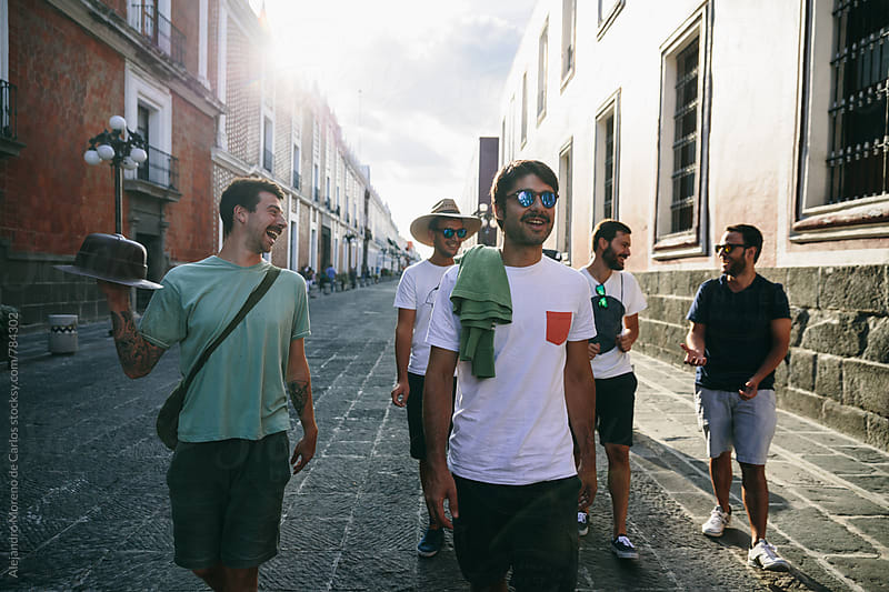 Front view of group of young confident men walking down a wide street by Alejandro Moreno de Carlos for Stocksy United