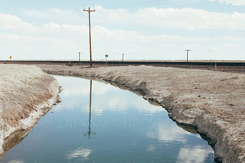 Canal and railroad tracks through vast desert, near Wendover, UT by Paul Edmondson for Stocksy United