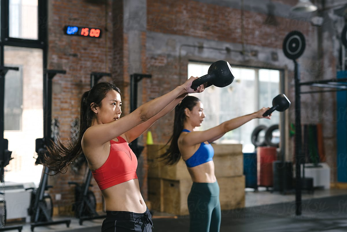 Asian Woman Lifting Weights In Gym by MaaHoo Studio - Dumbbell