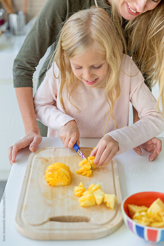 Smiling mother teaching her daughter how to cut fruit by Jovo Jovanovic for Stocksy United