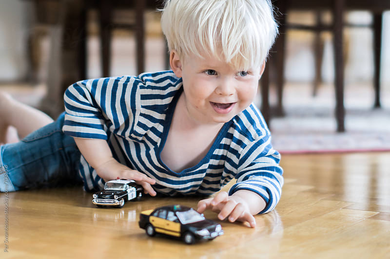 Happy 3 year old child paying with his toy cars  by Per Swantesson for Stocksy United