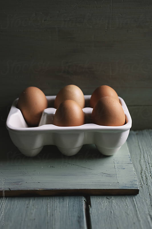 Five eggs in a ceramic egg carton.  by Darren Muir for Stocksy United
