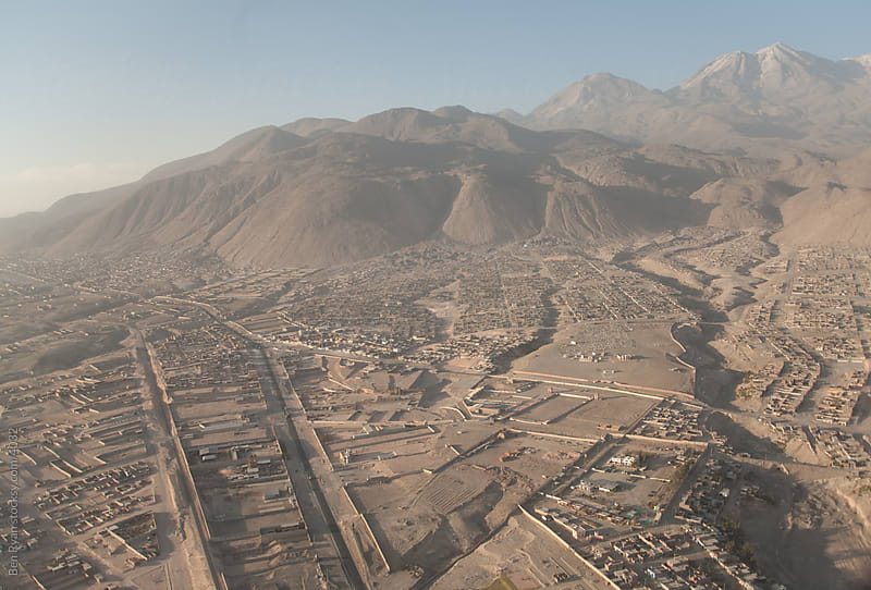 Aerial view of dusty city and sprawling volcano by Ben Ryan for Stocksy United
