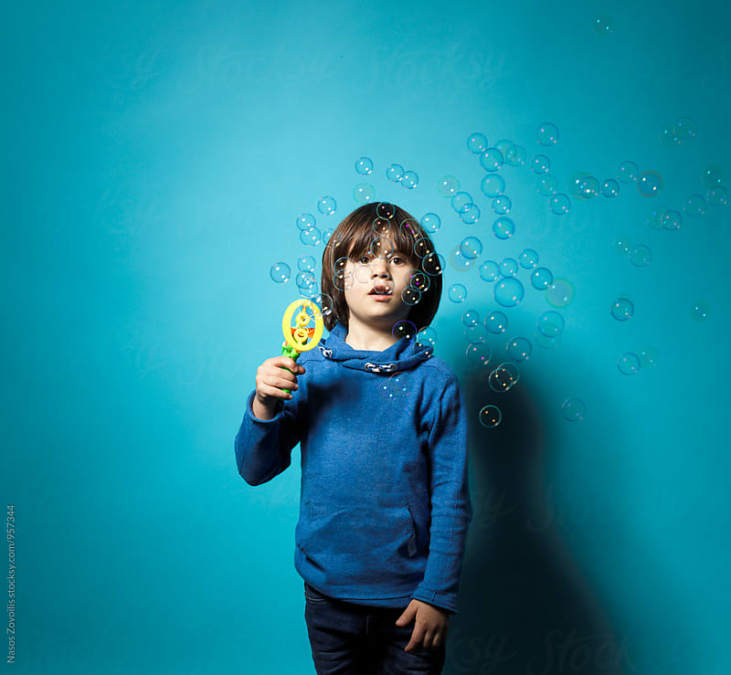 5 year old boy holding a pistol which blow soap bubbles by Nasos Zovoilis for Stocksy United