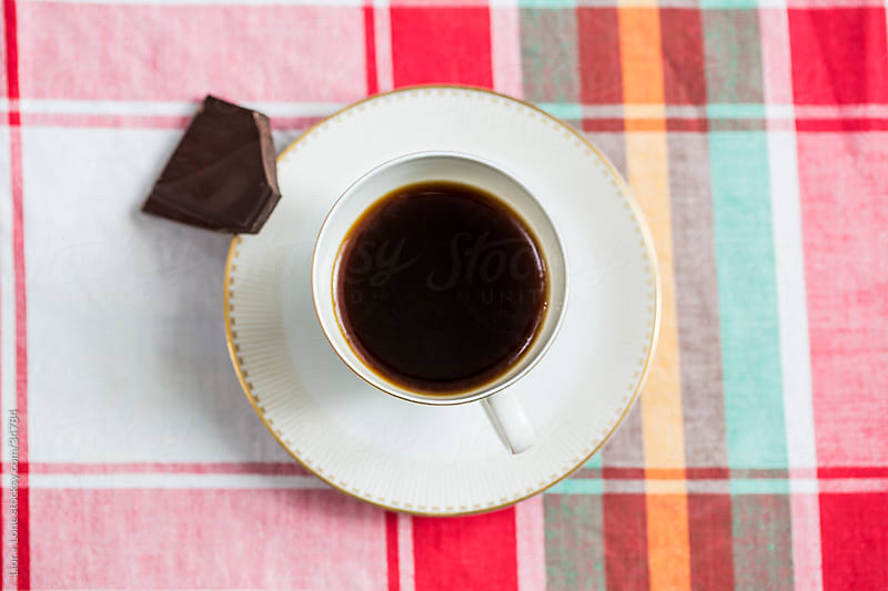 cup off black coffee on white saucer with dark chocolate  by Lior + Lone for Stocksy United