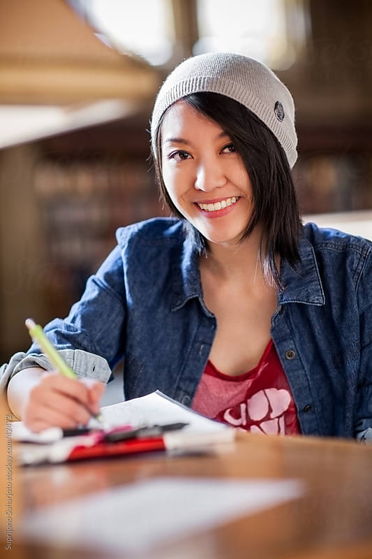 Smiling Asian college student studying in the library by Suprijono Suharjoto for Stocksy United