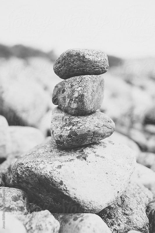 Balancing stones on top of each other by Jonas Räfling for Stocksy United
