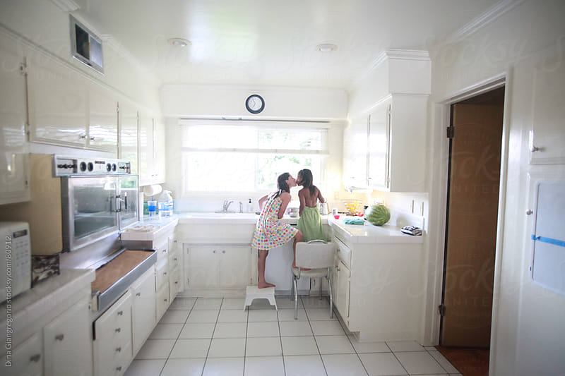 Two little girls standing on chairs in kitchen and kissing by Dina Giangregorio for Stocksy United