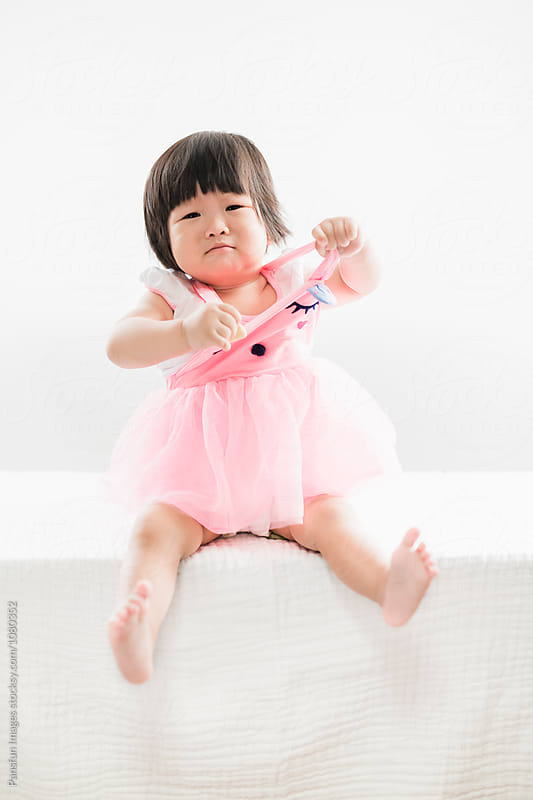 baby girl pulling skirt by Pansfun Images for Stocksy United