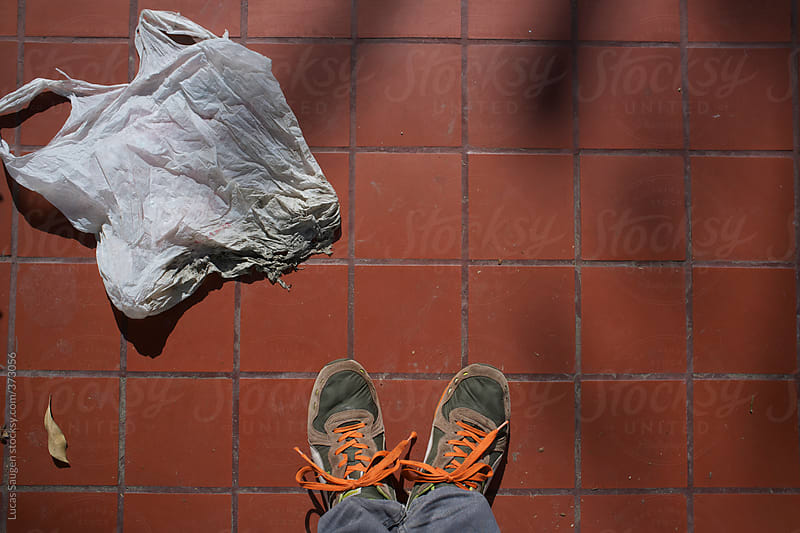 Looking down at my feet and an old plastic shopping bag. by Lucas Saugen for Stocksy United