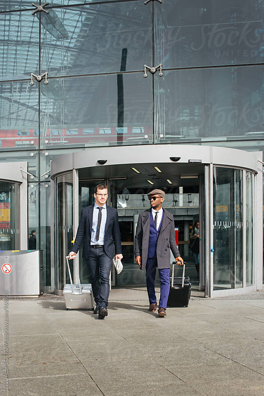 Two Male Business Travelers Walking Out of Large Modern Glass Building by Julien L. Balmer for Stocksy United