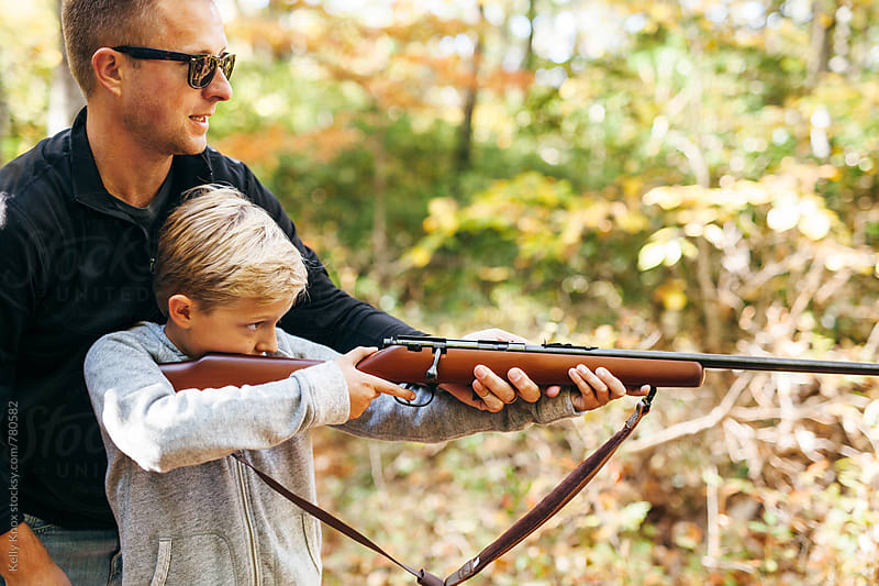 father helping his son to steady a rifle before shooting by Kelly Knox for Stocksy United