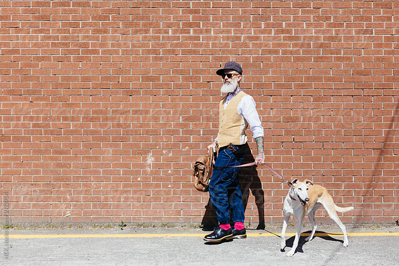 Stylish Old Man With Tattoos With His Pet . Dog by HEX. for Stocksy United