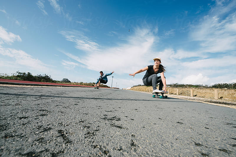 Couple on Skateboards  by Urs Siedentop & Co for Stocksy United