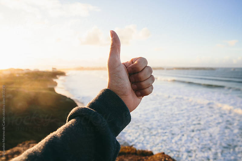 Male hand doing a thumbs up in front of beautiful scenic views of a natural sea shore at sunset by Alejandro Moreno de Carlos for Stocksy United
