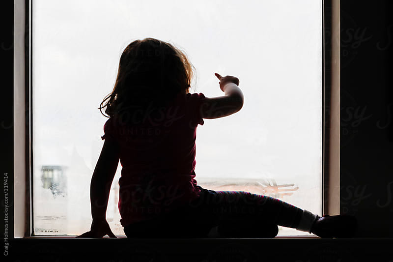 Four year old girl drawing on a window with her finger by Craig Holmes for Stocksy United