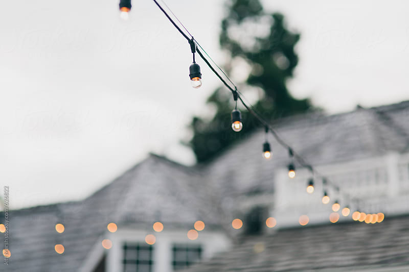 Lights strung outside a house by Jeff Marsh for Stocksy United