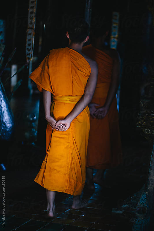 Young Buddhist monks walking in the temple, back view by michela ravasio for Stocksy United