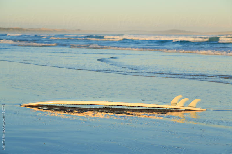 Surfboard on a beach. by John White for Stocksy United