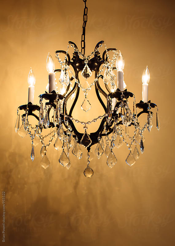 fancy chandelier on gold wall by Brian Powell for Stocksy United