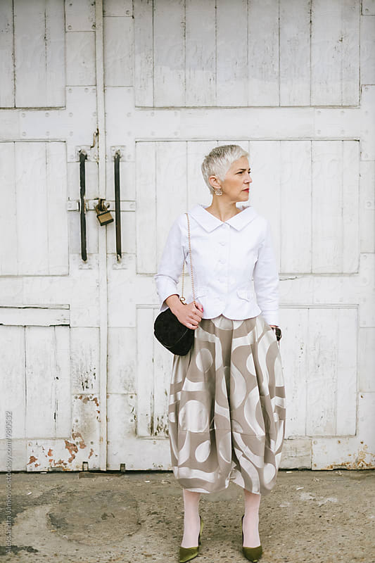 Fashionable Senior Woman Standing in Front of the White Door by Aleksandra Jankovic for Stocksy United