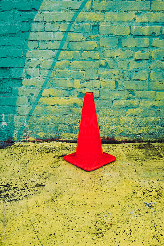 Traffic cone in front of colorfully painted brick wall by Paul Edmondson for Stocksy United