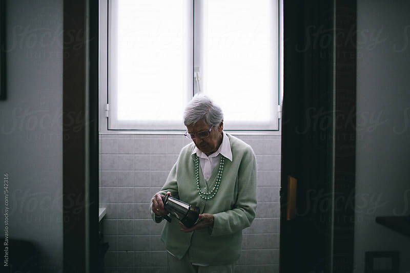 Elderly woman making coffee with mocha by michela ravasio for Stocksy United