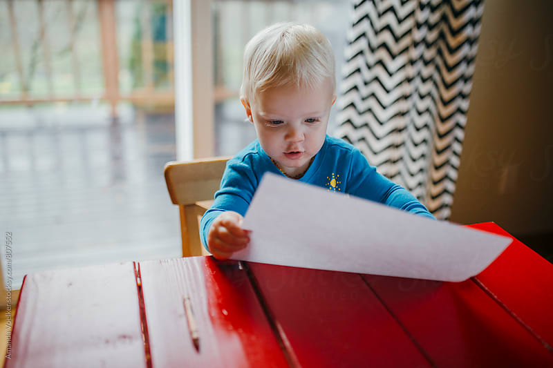 Blonde Toddler Boy Holds Up his Drawing Paper in Awe by Amanda Voelker for Stocksy United