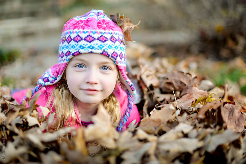 Little Girl Playing In Fall Leaf Pile in Autumn by JP Danko for Stocksy United