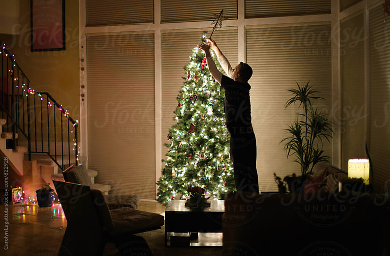 Man reaching up to put the star on the Christmas tree at night by Carolyn Lagattuta for Stocksy United