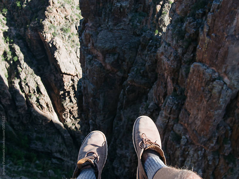 Man in leather boots dangling his feet over edge of cliff in Colorado by Jeremy Pawlowski for Stocksy United