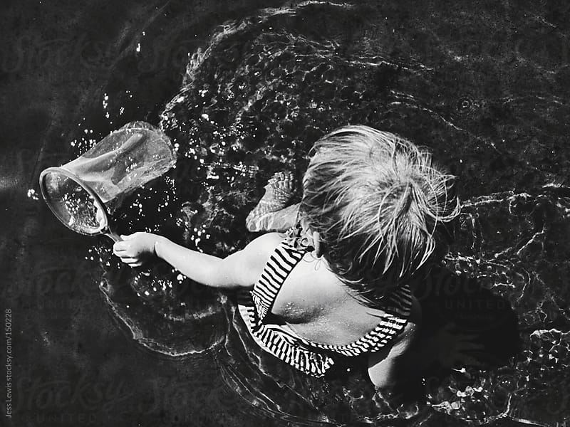 young girl playing with net in water by Jess Lewis for Stocksy United