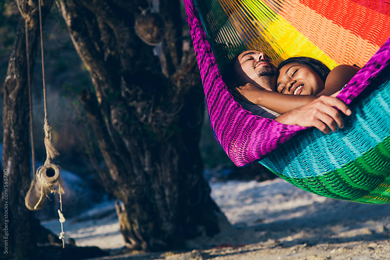 Young loving couple relaxing in hammock on sandy beach by the sea at sunset by Soren Egeberg for Stocksy United