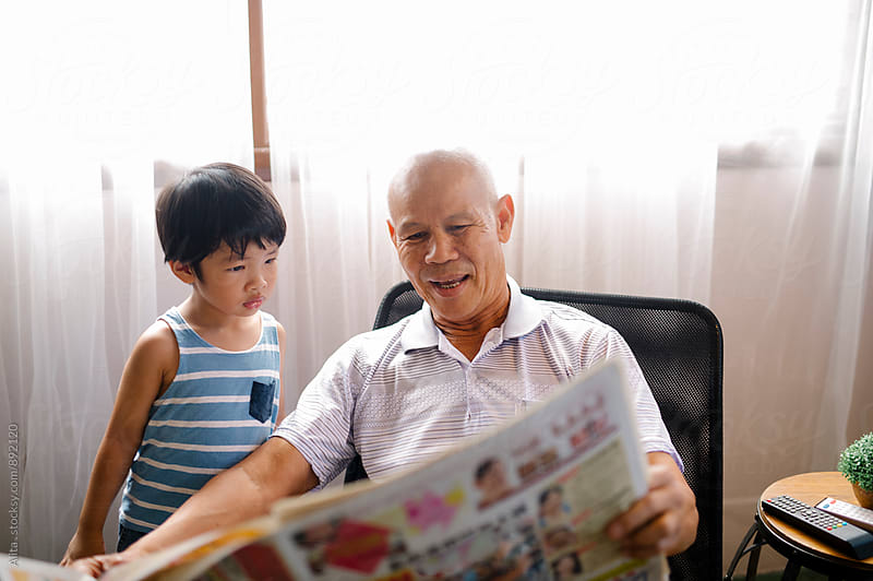 Grandpa and grandkid looking at newspaper by Alita Ong for Stocksy United
