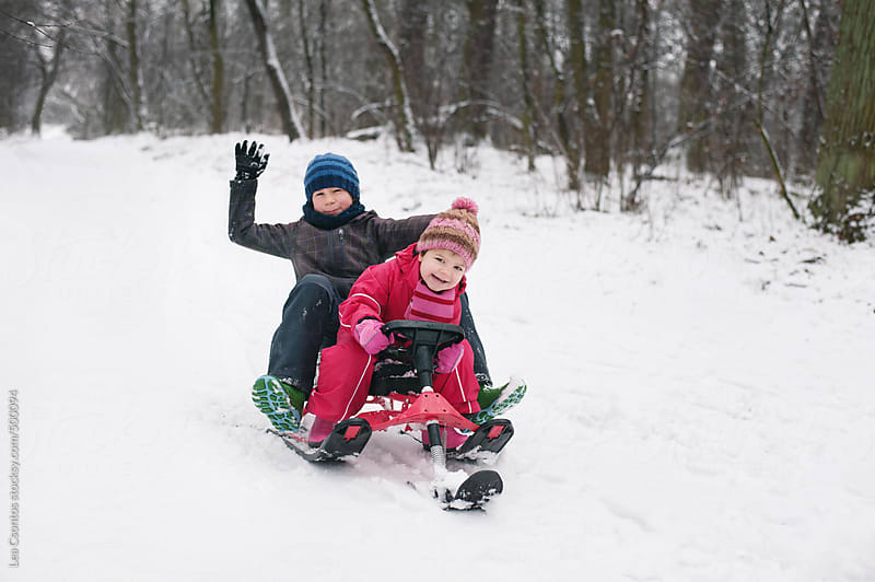 Children sitting and riding a sledge having fun in the snow. by Lea Csontos for Stocksy United