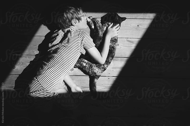 Boy and cat in the light.  by Kirstin Mckee for Stocksy United