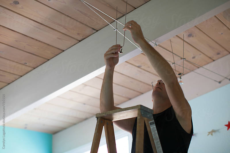 Man installing cable lighting in his home by Carolyn Lagattuta for Stocksy United