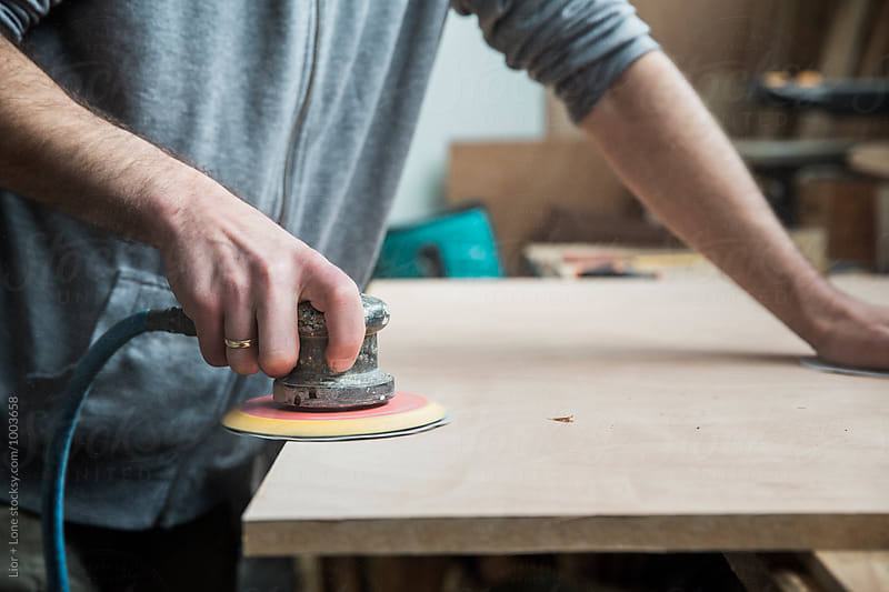 Carpenter using a pneumatic sander to smooth wood by Lior + Lone for Stocksy United