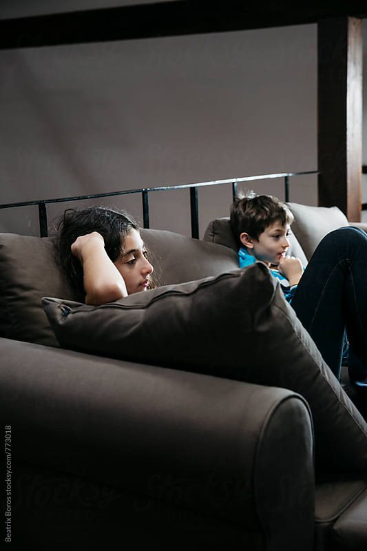 Kids sitting on the sofa watching tv by Beatrix Boros for Stocksy United