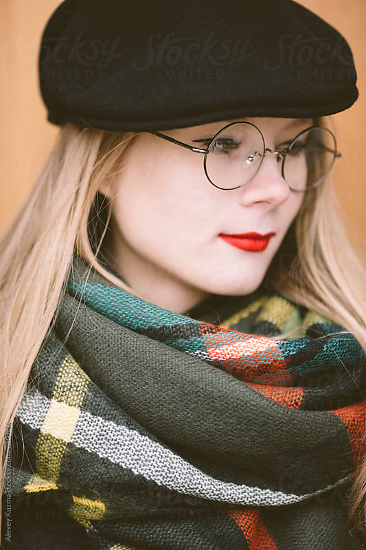 young woman with black hat  and round glasses by Alexey Kuzma for Stocksy United