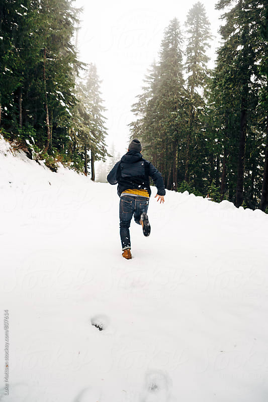 Man Running Through Snow Covered Road Between Pine Trees by Luke Mattson for Stocksy United
