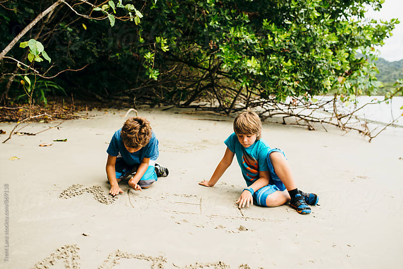 Two boys writing and playing on sandy beach by Trent Lanz for Stocksy United