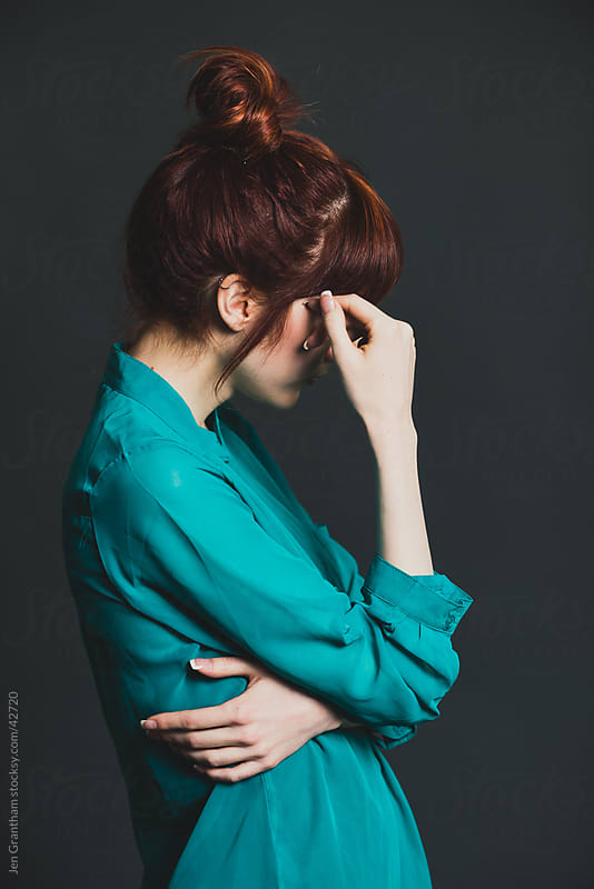 Side view of redheaded young woman covering her face by Jen Grantham for Stocksy United