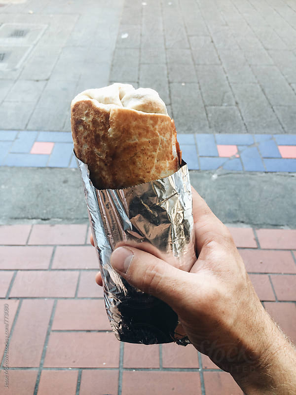 hand holding burrito street food wrapped in foil by Jesse Morrow for Stocksy United