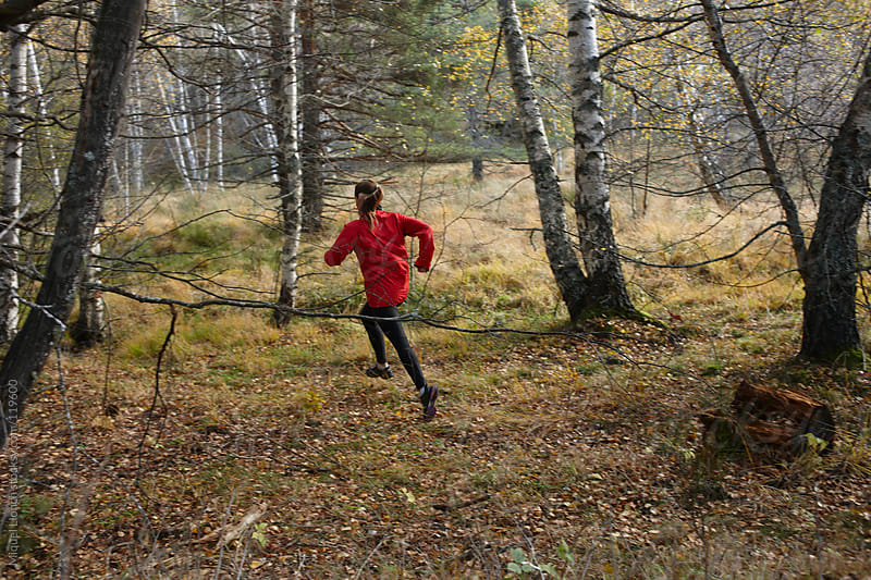 Young woman running in the forest by Miquel Llonch for Stocksy United
